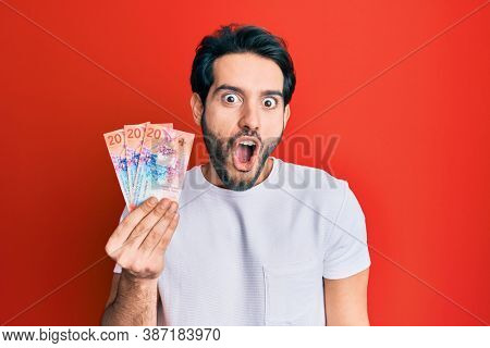 Young hispanic man holding swiss franc banknotes scared and amazed with open mouth for surprise, disbelief face