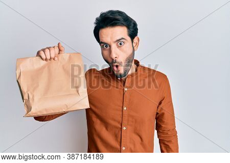 Young hispanic man holding take away food scared and amazed with open mouth for surprise, disbelief face
