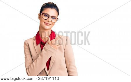 Young beautiful woman wearing business shirt and glasses cheerful with a smile of face pointing with hand and finger up to the side with happy and natural expression on face