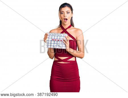 Young beautiful woman holding heart calendar scared and amazed with open mouth for surprise, disbelief face