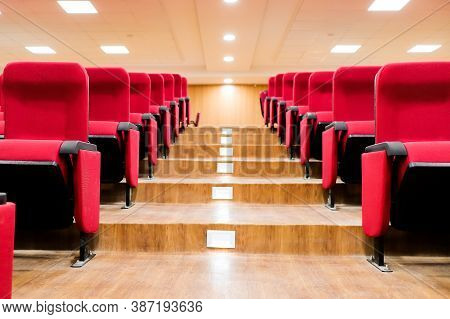 Stairscase Gallery Between Empty Rows Of Seats Of An Auditorium With Red Reclining Rows Of Seats And