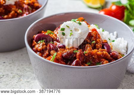 Chili Con Carne With Rice In A Gray Bowl. Beef Stew With Beans In Tomato Sauce With Sour Cream And R