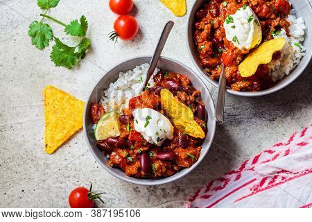Chili Con Carne With Rice, Sour Cream And Nachos In A Gray Bowl. Beef Stew With Beans In Tomato Sauc