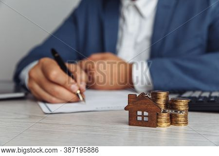 Sale Agent Approved Mortgage Loan Agreement Contract. Wooden House Shaped Keyring And Stack Of Coins