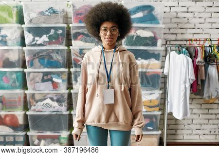 African American Woman Looking At Camera, Posing In Front Of Boxes Full Of Clothes, Young Volunteer