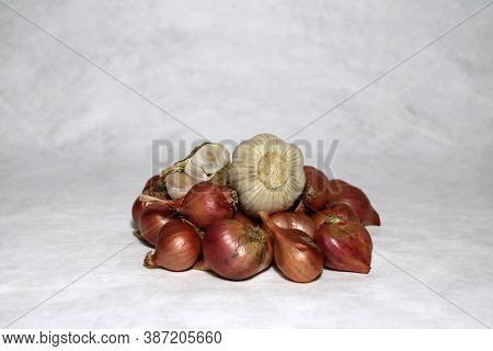 Garlic On The Stack Of Shallots On White Background.