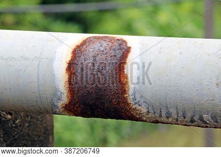 Antique Rust Water Pipes For Village Hydrant Water On Green Background. A Pipe For Conveying Water S