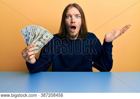 Handsome caucasian man with long hair holding dollars scared and amazed with open mouth for surprise, disbelief face