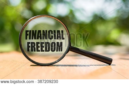 Magnifier Glass With Text Financial Freedom On Wooden Table. Business Concept