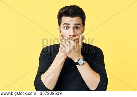 Shocked Man Covering Mouth With Hands Over Yellow Background. Emotions And Secret Concept