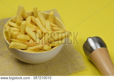 Portion Of Potato Fries In Ceramic Bowl On Yellow Background