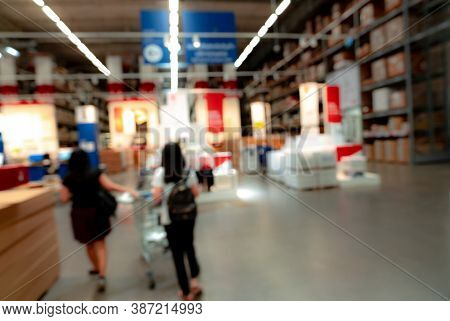 Blurred Two Woman Shopping Goods At Self-service Warehouse Of Store. Woman Pushing A Shopping Cart I