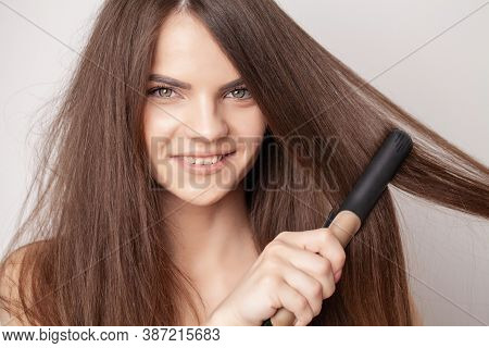 Beautiful Woman Straightens Her Hair With A Curling Iron