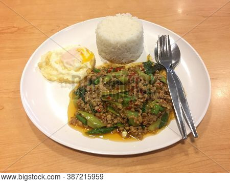 Fried Minced Pork With Basil Leaves And Fried Egg With Rice In The White Dish With Cutlery On The Wo