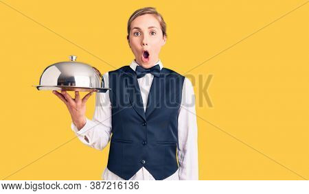 Young beautiful blonde woman wearing waitress uniform holding tray scared and amazed with open mouth for surprise, disbelief face