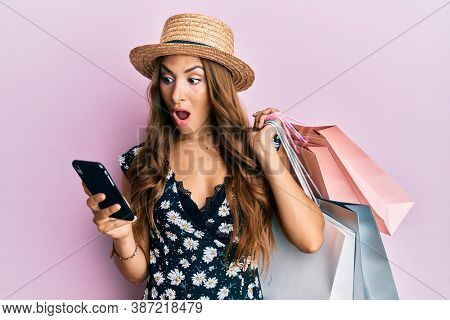 Young brunette woman holding shopping bags and smartphone afraid and shocked with surprise and amazed expression, fear and excited face.