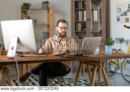Young serious male freelance designer looking at laptop display while having drink and using tablet and stylus for drawing new logo