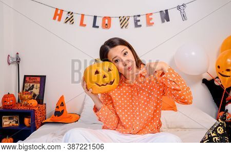 Asian Woman Holding Pumpkin Face For Halloween Festival At Home. Bedroom Decoration For Kid And Fami