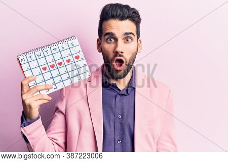 Young handsome man with beard holding calendar with hearts scared and amazed with open mouth for surprise, disbelief face