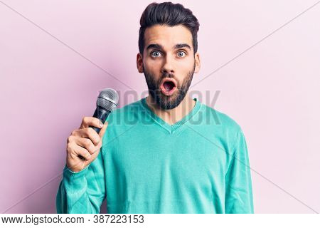 Young handsome man with beard singing song using microphone scared and amazed with open mouth for surprise, disbelief face