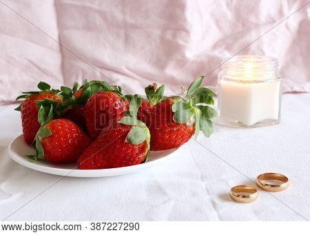 Bright Wedding Scene, Porcelain Plate With Fresh Strawberries And Wedding Rings A White Background.