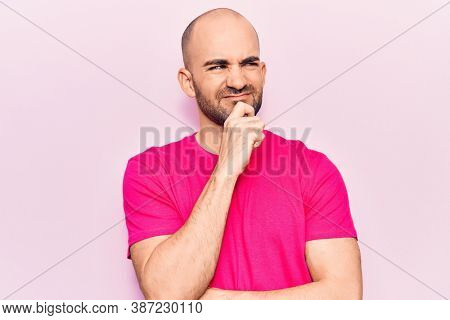 Young handsome bald man wearing casual t shirt thinking concentrated about doubt with finger on chin and looking up wondering