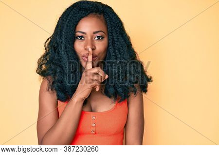Beautiful african woman wearing casual clothes asking to be quiet with finger on lips. silence and secret concept.