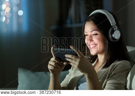 Happy Woman Wearing Headphones Watching Videos On Smart Phone In The Night Sitting On A Couch In The