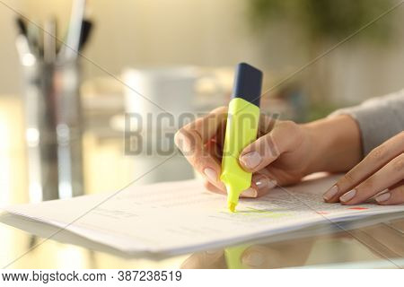 Close Up Of A Woman Hand Underlining Text On Document With Marker On A Desk At Home