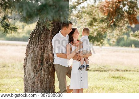 Dad, Mom Hugging Son Outdoors In The Park. The Concept Of Summer Holiday. Mothers, Fathers, Babys Da