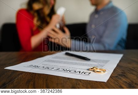 Divorce Decree Document. Man Calms Down A Woman On The Background.