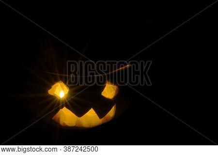 Halloween Pumpkin Smile And Scary Eyes For A Party, Jack Lantern Isolated On Black Background