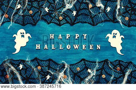 Halloween background. Happy Halloween letters and Halloween decorations on the dark blue wooden background, Happy Halloween festive concept