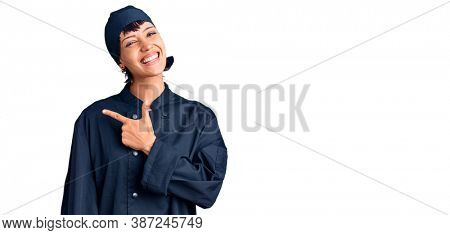 Young brunette woman with short hair wearing professional cook uniform cheerful with a smile of face pointing with hand and finger up to the side with happy and natural expression on face