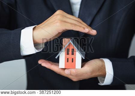 A House Model In The Hands Of A Businessman To Protect Home Protection Concept Using Real Estate Inv