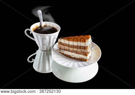 White Cup Of Coffee With Spoon And Steam, And Saucer With Flaky Cake On Mirror Surface On Black Back