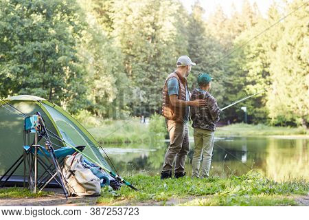 Back View Full Length Portrait Of Loving Father Teaching Son Fishing While Enjoying Camping Trip Tog