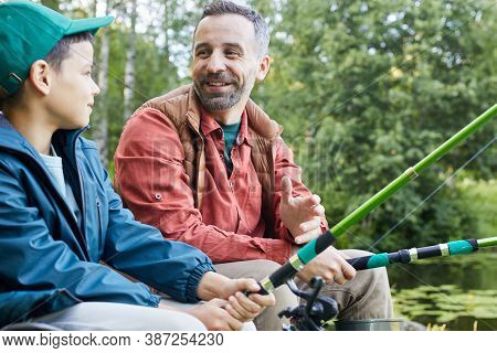 Portrait Of Happy Father Enjoying Fishing With Little Son During Camping Trip By Lake
