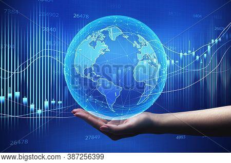 Global Economy. Female Hand Holding World Globe Over Blue Background With Economic Financial Graphs