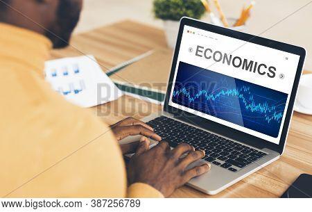 Economics. African American Businessman Working On Laptop Analyzing Economic Graphs And Statistics C