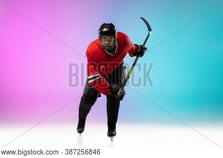 On Fire. Male Hockey Player With The Stick On Ice Court And Neon Gradient Background. Sportsman Wear