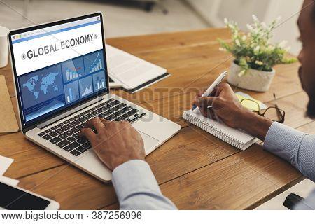 Global Economy. African Business Man At Laptop Working Analyzing Economic Statistics Graphs Sitting