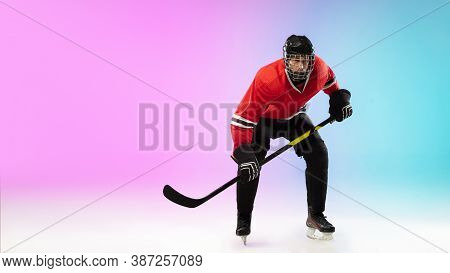 Attack. Male Hockey Player With The Stick On Ice Court And Neon Gradient Background. Sportsman Weari