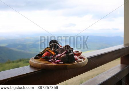 Shish Kebab On A Wooden Board Against A Background Of Mountains.shish Kebab With Grilled Vegetables