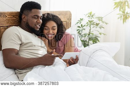 Happy Black Lovers Holding Smartphone, Watching Photos Or Videos Together, Lying On Bed At Home, Cop