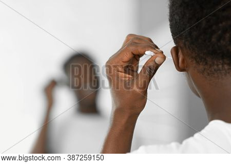 Black Man Cleaning Ears Using Cotton Swab Standing In Bathroom At Home. Clean Ear And Safe Earwax Re