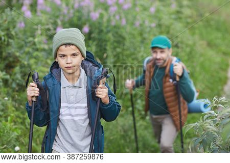 Portrait Of Happy Father And Son Hiking Together And Walking Uphill, Focus On Smiling Boy With Hikin
