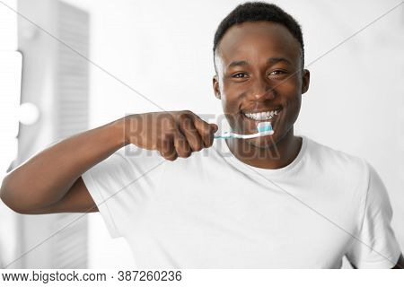African Guy Brushing Teeth With Toothbrush Standing In Modern Bathroom At Home In The Morning, Smili