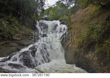 Between The Mountain Slopes A Waterfall Rages And Foams On The Stones. Tropical Trees Grow Around. V