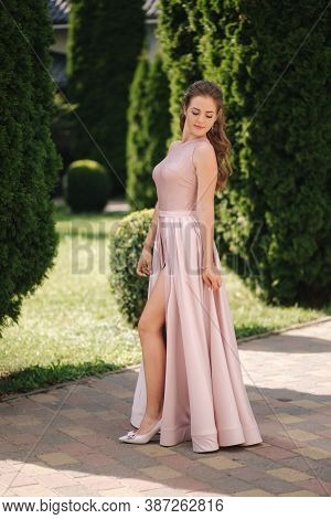 Beautiful Young Woman Spin Arround In Gorgeous Evening Dress, Background Of Green Thee